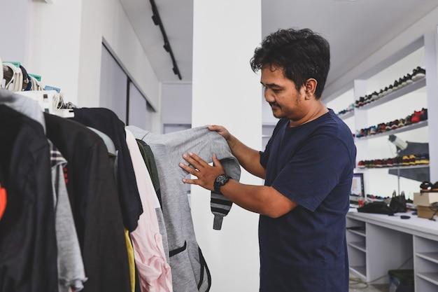패션 매장에서 선반에 옷을 선택하는 젊은 남성