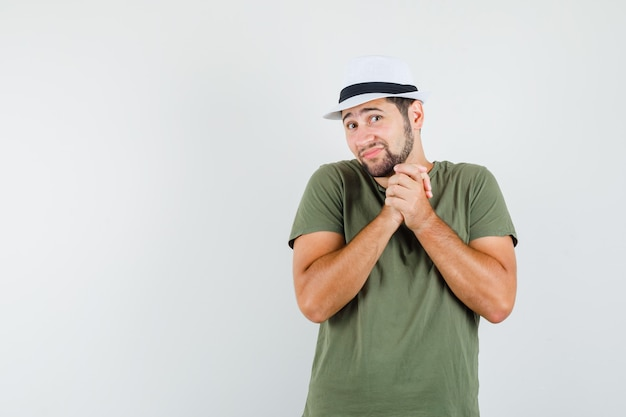緑のtシャツと帽子でジェスチャーを祈って手を握りしめ、希望に満ちた若い男性