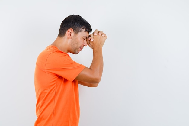 オレンジ色のtシャツで祈りのジェスチャーで手を握りしめ、希望に満ちた若い男性。
