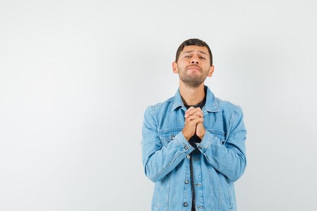 若い男性がtシャツのジャケットでジェスチャーを祈って手を握りしめ、希望を持って見える