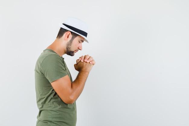 緑のtシャツと帽子で捕食ジェスチャーで手を握りしめ、希望に満ちた若い男性。 。