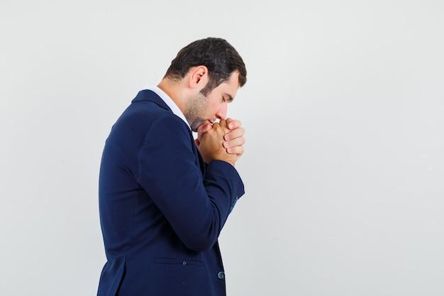Giovane maschio stringendo le mani nel gesto di preghiera in camicia e giacca e guardando speranzoso.