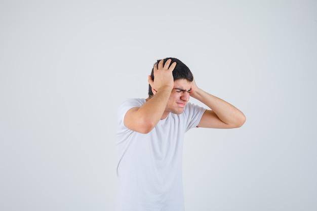 Giovane maschio stringendo la testa con le mani in maglietta e guardando stressato. vista frontale.