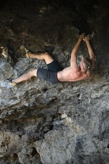 Молодой мужчина-альпинист боулдеринг на каменной стене в пещере