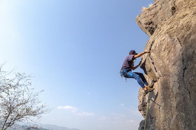 Молодой мужчина-альпинист на скалистом утесе на фоне голубого неба