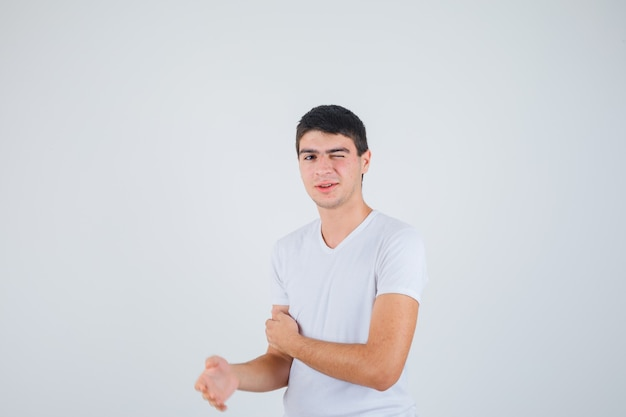 Tシャツを着たカメラを見て、おかしな顔をしながら片目を閉じる若い男性。正面図。