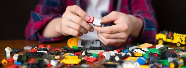 Молодой самец построить игрушечные кирпичи на деревянном столе детская игрушка детство b