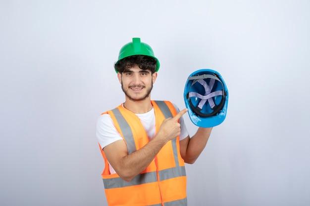 Молодой мужской рабочий-строитель, держа защитный шлем на белом фоне. фото высокого качества