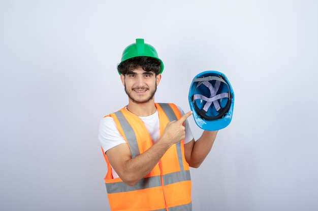 Young male construction worker holding hardhat on white background. high quality photo