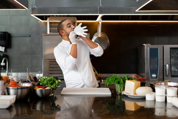 Young male cook blows up his protective glove jokes and has fun in the professional kitchen