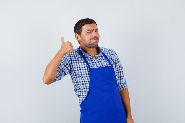 Giovane cuoco maschio in un grembiule blu e una camicia