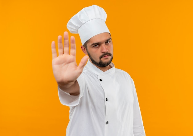 Young male cook in chef uniform gesturing stop  isolated on orange space