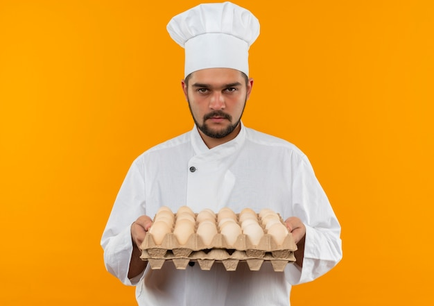 Young male cook in chef uniform holding carton of eggs and looking  isolated on orange space