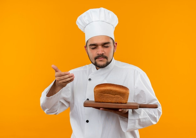 Young male cook in chef uniform holding cutting board with bread on it and sniffing with hand on air and closed eyes isolated on orange space