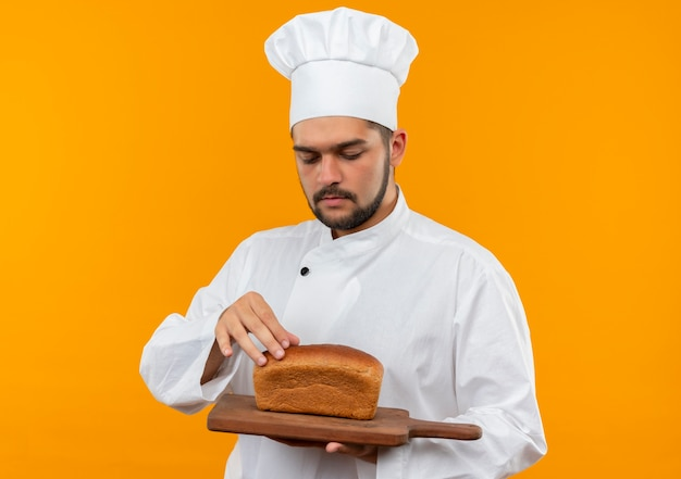 Young male cook in chef uniform holding cutting board with bread on it and touching bread isolated on orange space