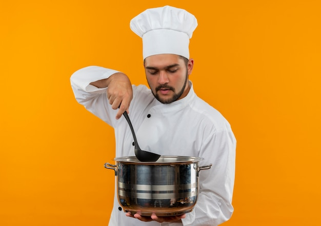 Young male cook in chef uniform holding ladle and pot looking inside of pot isolated on orange space