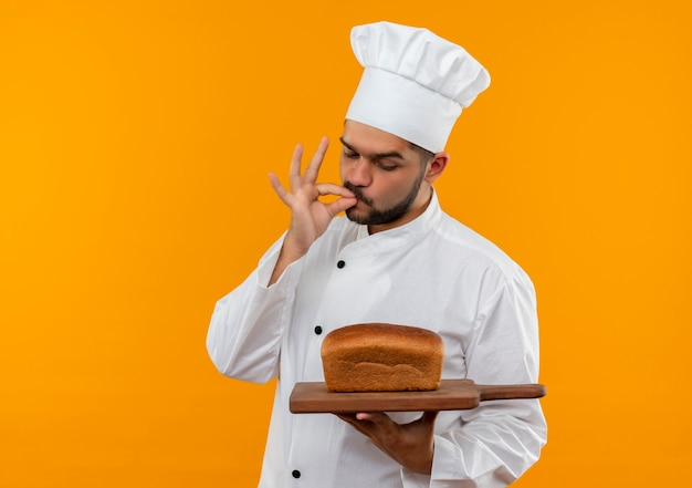 Young male cook in chef uniform holding and looking at cutting board with bread on it and doing tasty gesture isolated on orange space