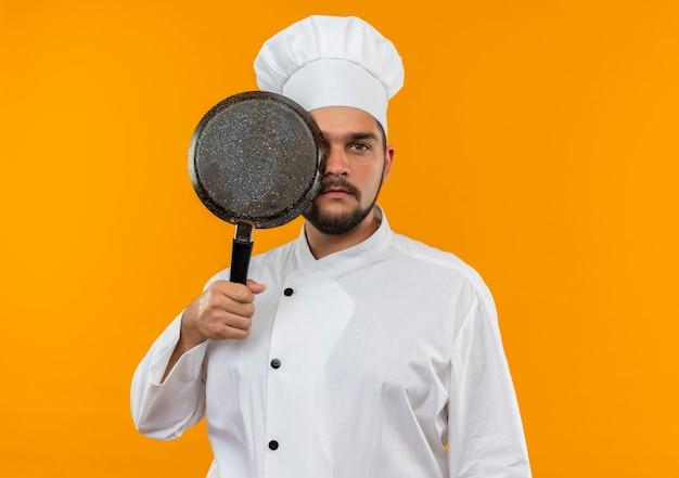 Giovane cuoco maschio in uniforme del cuoco unico che tiene e che osserva da dietro la padella isolata sullo spazio arancione
