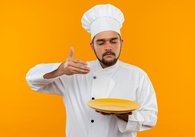 Young male cook in chef uniform holding plate and sniffing with hand on air and closed eyes isolated on orange space