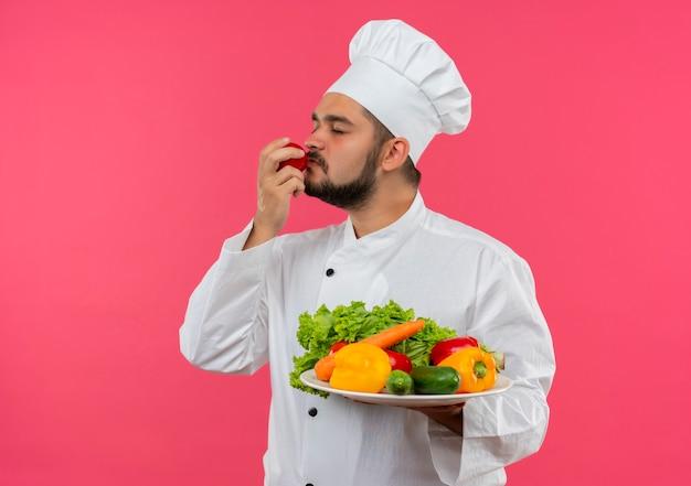 Giovane cuoco maschio in uniforme del cuoco unico che tiene piatto di verdure e annusando il pomodoro con gli occhi chiusi isolati su spazio rosa