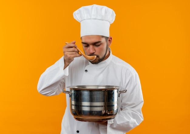 Giovane cuoco maschio in pentola uniforme della holding del cuoco unico e mangiare dal cucchiaio isolato sullo spazio arancione