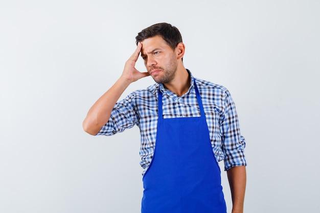 青いエプロンとシャツを着た若い男性料理人