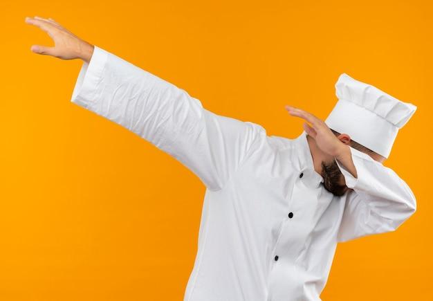 オレンジ色のスペースで隔離の軽くたたくジェスチャーをしているシェフの制服を着た若い男性料理人