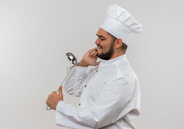 鍋を保持し、ピンクのスペースで隔離の鏡としてそれを使用してシェフの制服を着た若い男性料理人