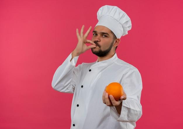 Молодой мужчина-повар в униформе шеф-повара держит апельсин и делает вкусный жест, выглядя изолированным на розовом пространстве