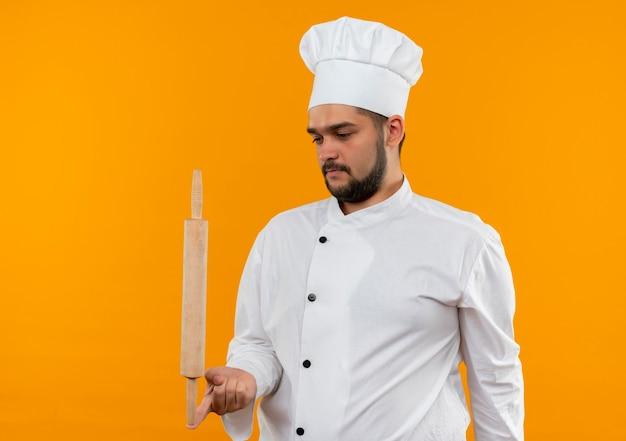 Молодой мужчина-повар в униформе шеф-повара держит скалку на пальце и смотрит на нее, изолированной на оранжевом пространстве