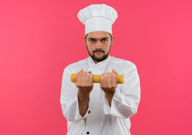 ピンクのスペースで隔離のスパゲッティパスタを保持しているシェフの制服を着た若い男性料理人