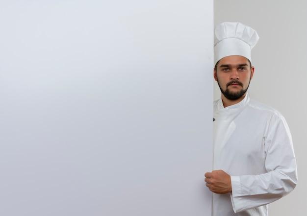 握りこぶしで見ている白い壁の後ろに立っているシェフの制服を着た若い男性料理人