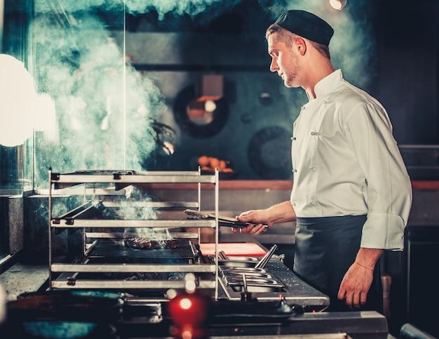 Молодой самец готовит еду на гриле на кухне
