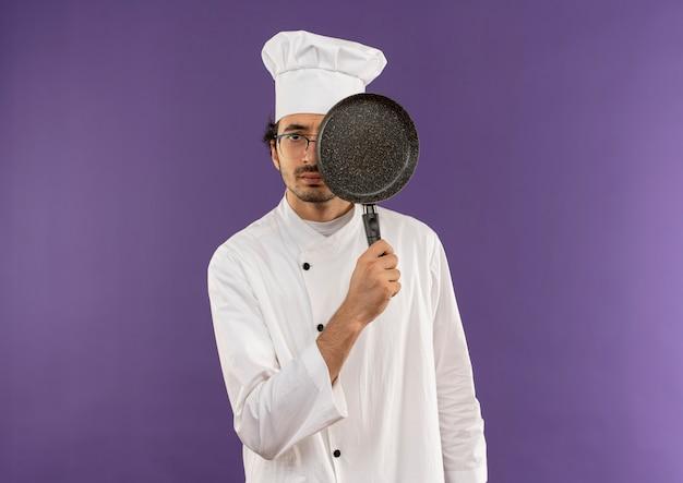 요리사 유니폼과 안경을 착용하는 젊은 남성 요리사는 프라이팬으로 눈을 덮었습니다.