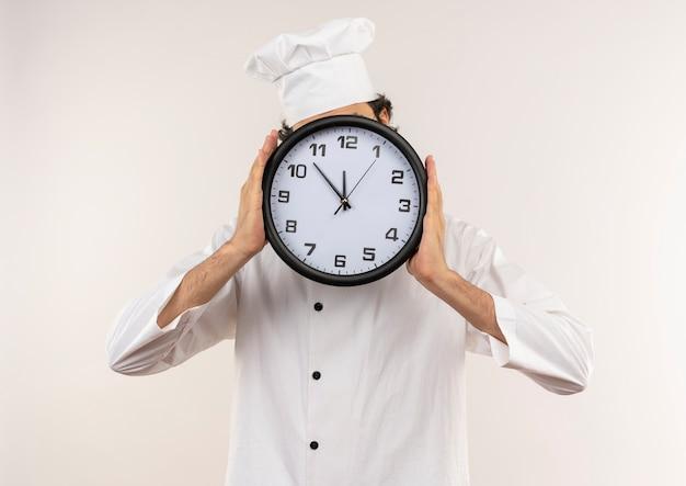 シェフの制服と白い壁に分離された壁時計で顔を覆った眼鏡を身に着けている若い男性料理人