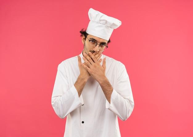 シェフの制服と眼鏡をかけた若い男性料理人が手で口を覆った