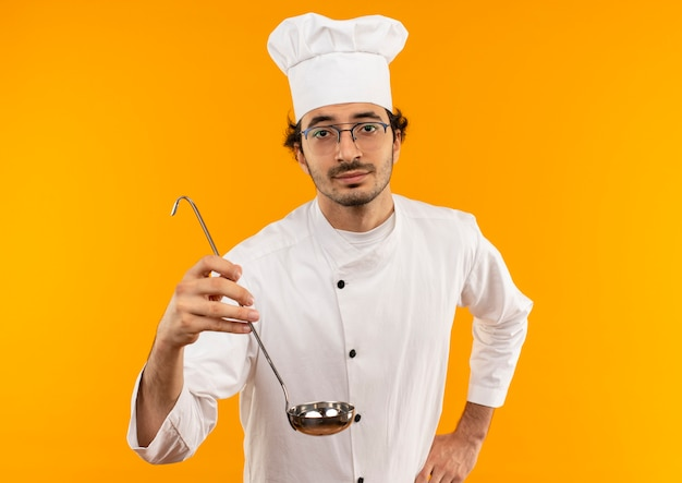 シェフの制服と腰に手を置いて鍋を差し出す眼鏡を身に着けている若い男性料理人