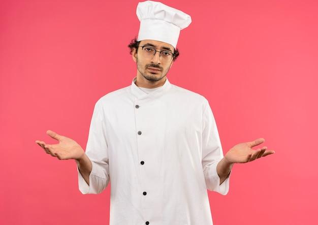 シェフの制服とメガネを身に着けている若い男性料理人は、どのようなジェスチャーを示しています