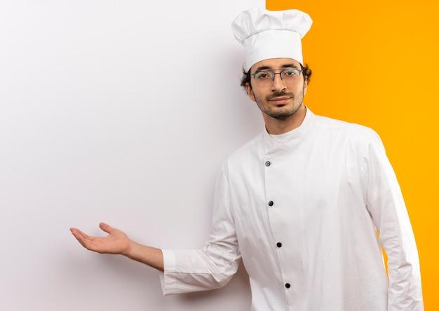 シェフの制服と白い壁の手で示す眼鏡を身に着けている若い男性料理人