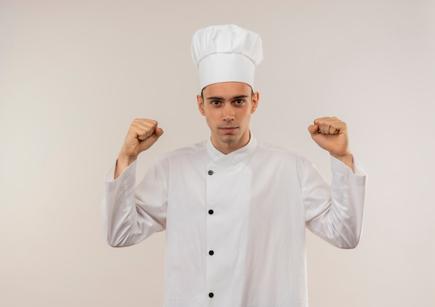 Young male cook wearing chef uniform doing strong gesture on isolated white wall