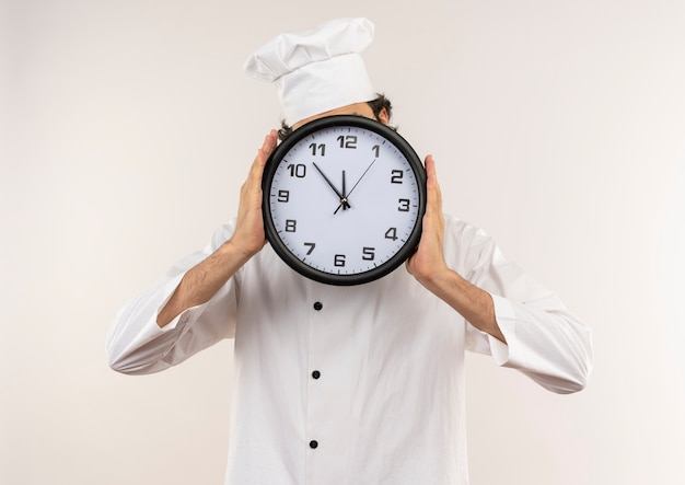 Young male cook wearing chef uniform and glasses covered face with wall clock isolated on white wall