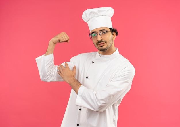Giovane cuoco maschio che indossa l'uniforme dello chef e bicchieri facendo un gesto forte