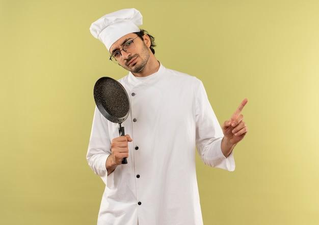 Giovane cuoco maschio che indossa l'uniforme dello chef e bicchieri tenendo la padella e punti a lato