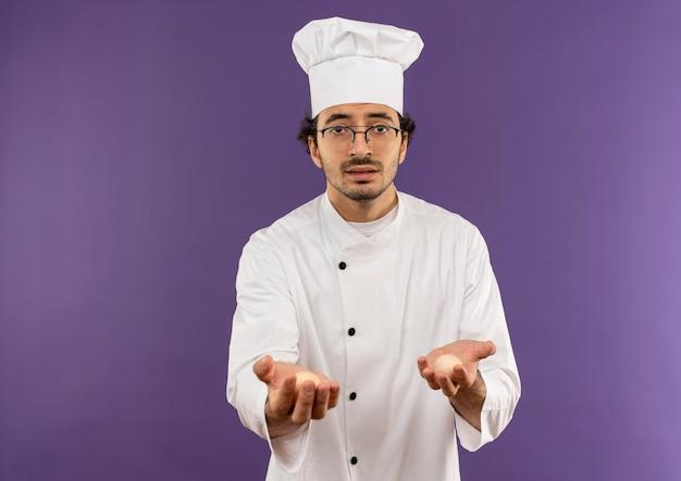 Giovane cuoco maschio che indossa l'uniforme dello chef e bicchieri tenendo fuori le uova