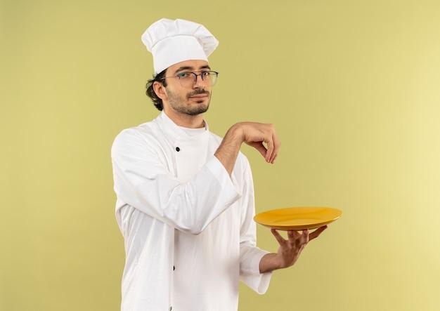 Giovane cuoco maschio indossa divisa da chef e bicchieri tenendo il piatto e fingendo di versare sale