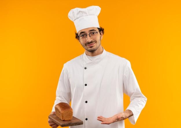 Giovane cuoco maschio che indossa l'uniforme dello chef e bicchieri di contenimento e punti con la mano per il pane sul tagliere