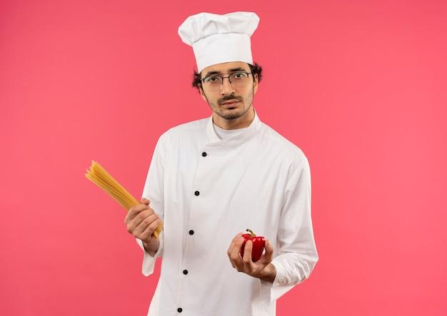 Giovane cuoco maschio indossa uniforme da chef e bicchieri tenendo spaghetti e pepe
