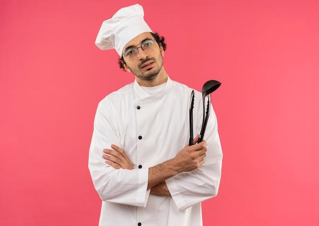 Giovane cuoco maschio che indossa l'uniforme dello chef e bicchieri tenendo la spatola e incrociando le mani