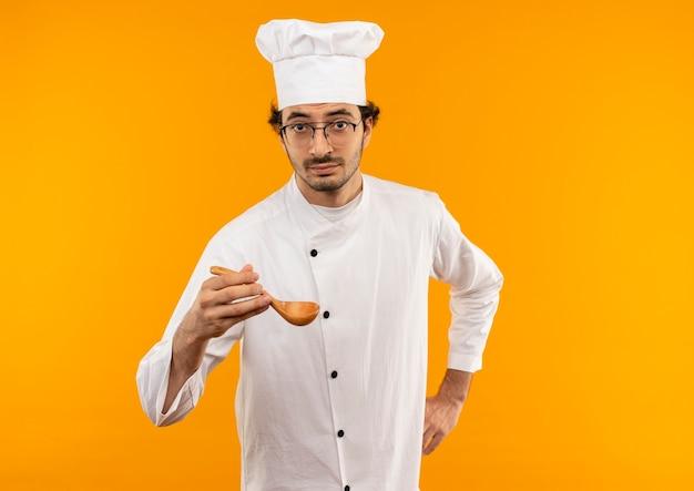 Giovane cuoco maschio che indossa l'uniforme dello chef e bicchieri tenendo il cucchiaio mettendo la mano sul fianco
