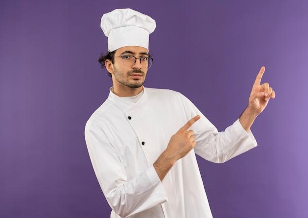 Giovane cuoco maschio che indossa l'uniforme dello chef e gli occhiali indica di lato
